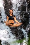 Beautiful woman sitting in natural waterfall Stock Photography