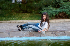 Beautiful woman sitting near the fountain in the Park Royalty Free Stock Images