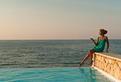 Beautiful woman sitting near infinity pool Royalty Free Stock Images