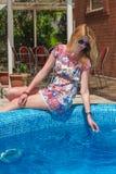 Beautiful woman sitting near the pool Stock Image