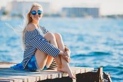 Beautiful woman sitting near the sea stock image