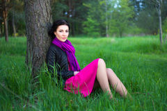 Beautiful woman sitting near the tree in summer forest Stock Photos