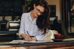 Beautiful woman sitting near a window at cafe and making some important notes in her book. Caucasian female writing in book at. Coffee shop royalty free stock photo
