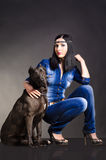 Beautiful woman sitting next to the dog. Beautiful woman in denim clothes sitting next to the dog Royalty Free Stock Photography