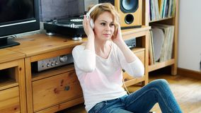 Woman sits next to the turntable and listens to music. Beautiful woman sitting next to a turntable with headphones on her head and listens to music stock video