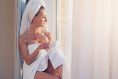 Beautiful woman sitting next to the window, enjoying sunrise after taking shower Stock Images
