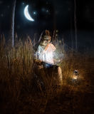 Beautiful woman sitting at night forest and reading fairy tale b Royalty Free Stock Images