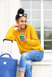 Beautiful woman sitting outdoor with suitcase and mobile phone Stock Photo