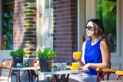 Beautiful woman sitting in outdoors cafe at Stock Images