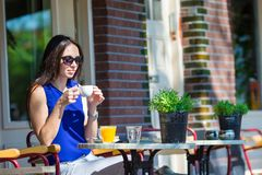 Beautiful woman sitting in outdoors cafe at Royalty Free Stock Photos
