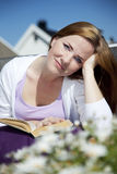 Beautiful woman reading. A beautiful woman sitting outside in the sun on a balcony. Looking into the camera with a smile with a book in her lap Royalty Free Stock Photo