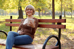 Beautiful woman sitting in park Stock Image