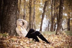 Beautiful woman sitting in a park in autumn Royalty Free Stock Photos