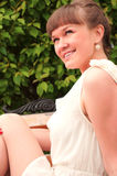 A beautiful woman is sitting on a park bench Stock Photo