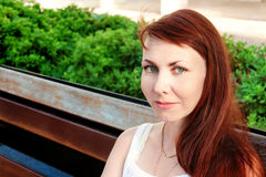 Beautiful woman is sitting on a park bench Stock Photos