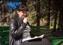Beautiful woman sitting on a park bench holding a pen and notebo Royalty Free Stock Image