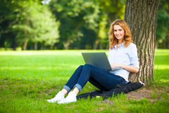 Beautiful woman sitting in park with laptop Royalty Free Stock Photography