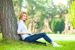 Beautiful woman sitting in park with laptop Royalty Free Stock Images