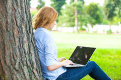 Beautiful woman sitting in park with laptop Royalty Free Stock Image