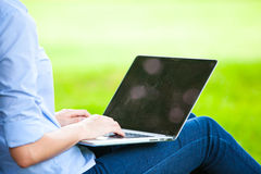 Beautiful woman sitting in park with laptop Stock Image