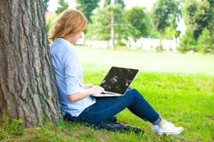 Beautiful woman sitting in park with laptop Royalty Free Stock Photos