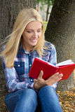 Beautiful woman sitting in park and reading book Royalty Free Stock Photography