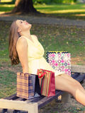 Beautiful woman sitting in the park after shopping Stock Photography