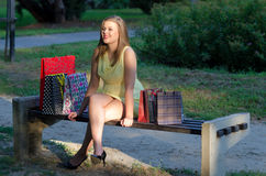 Beautiful woman sitting in the park after shopping Stock Images