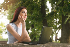 Beautiful woman sitting in the park, using a laptop. Beautiful young woman sitting in the park, using a laptop Stock Photo