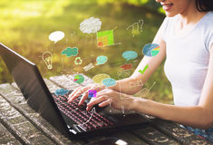 Beautiful woman sitting in the park, using a laptop Stock Images