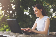 Beautiful woman sitting in the park, using a laptop Stock Photo