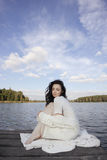 Beautiful woman sitting on the pier. Fashion shot of beautiful woman wearing white sitting alone on the pier Stock Image