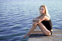 Beautiful woman sitting on a pier Stock Image