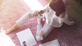 Beautiful woman sitting on pink carpet on the floor at modern light coloured living room and using electronic gadgets. Top view Royalty Free Stock Image