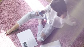 Beautiful woman sitting on pink carpet on the floor at modern light coloured living room and using electronic gadgets. Top view.Flare Stock Photography