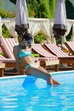 Beautiful Woman sitting by the pool Stock Image
