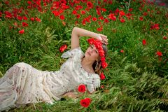 Beautiful  woman sitting in the poppy flower Royalty Free Stock Photo