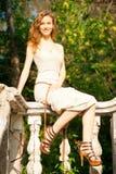 Beautiful woman sitting on railing Stock Photography