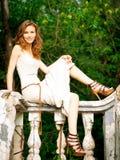 Beautiful woman sitting on railing Royalty Free Stock Photography