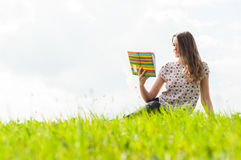 Beautiful woman sitting and reading a book on grass Royalty Free Stock Photography