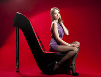 Beautiful woman sitting on the red high heel sofa. Beautiful woman sitting on the red high heel woman shoe sofa Stock Photo