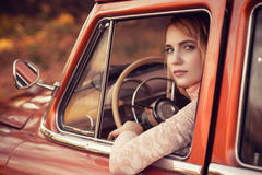 Beautiful woman sitting in red retro car Royalty Free Stock Image