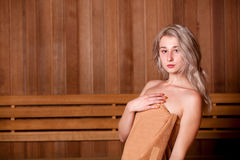 Beautiful woman sitting relaxed in a wooden sauna   brown towel Stock Photography