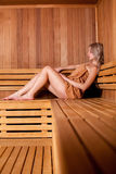Beautiful woman sitting relaxed in a wooden sauna   brown towel Royalty Free Stock Photos