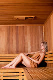 Beautiful woman sitting relaxed in a wooden sauna   brown towel Royalty Free Stock Images