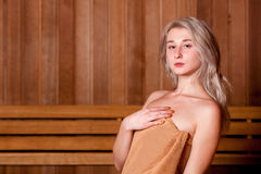 Beautiful woman sitting relaxed in a wooden sauna   brown towel Royalty Free Stock Photo