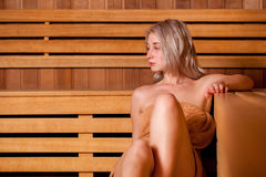 Beautiful woman sitting relaxed in a wooden sauna   brown towel Royalty Free Stock Image
