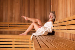 Beautiful woman sitting relaxed in a wooden sauna white coat Royalty Free Stock Image