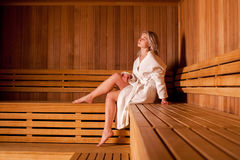 Beautiful woman sitting relaxed in a wooden sauna white coat Stock Photo