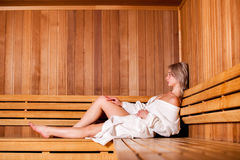 Beautiful woman sitting relaxed in a wooden sauna white coat Royalty Free Stock Photo